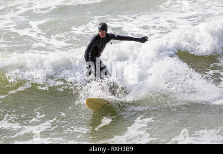 Bournemouth, Dorset, UK. 10th Mar 2019. UK weather: big waves and plenty of surf create ideal surfing conditions for surfers at Bournemouth beach on a windy day with some sunshine. Surfer on surf board in the waves.   Credit: Carolyn Jenkins/Alamy Live News - Stock Photo