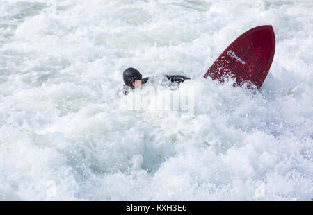 Bournemouth, Dorset, UK. 10th Mar 2019. UK weather: big waves and plenty of surf create ideal surfing conditions for surfers at Bournemouth beach on a windy day with some sunshine. Surfer and surf board in the waves.   Credit: Carolyn Jenkins/Alamy Live News - Stock Photo