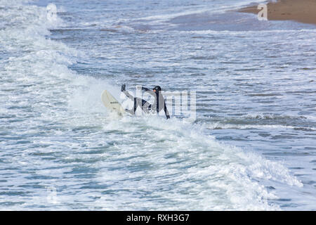 Bournemouth, Dorset, UK. 10th Mar 2019. UK weather: big waves and plenty of surf create ideal surfing conditions for surfers at Bournemouth beach on a windy day with some sunshine. Surfer falling from surf board in the waves.   Credit: Carolyn Jenkins/Alamy Live News - Stock Photo