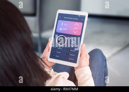 Smart home control automation app concept. Woman use tablet with modern flat desing app to control living room temperature, ventilation, lighting. - Stock Photo