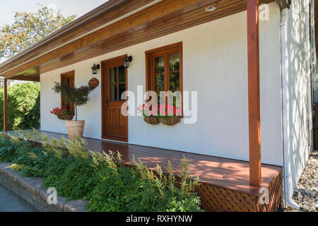 Old 1877 French regime style house facade with white stucco finish, reddish brown stained period reproduction wooden windows in summer, Quebec, Canada - Stock Photo