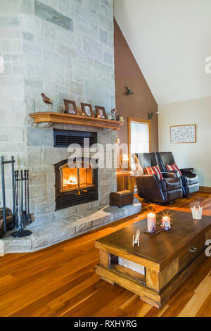 Grey cut stone lit fireplace in living room with brown leather reclining armchairs, timber wood coffee table, and cherrywood floorboards inside an old - Stock Photo