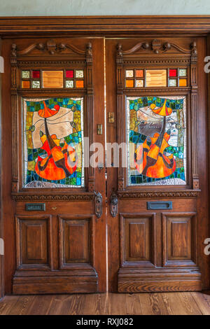 Old wooden doors with stained glass windows and carved details in living room inside an old 1826 cottage style fieldstone house, Quebec, Canada. This  - Stock Photo