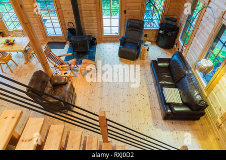 Looking down at the living room with brown leather reclining armchairs, sofa, dining table and black cast iron wood burning stove from the mezzanine i - Stock Photo