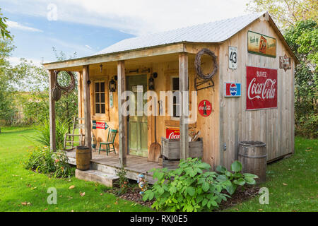 Old rustic pinewood plank cladded storage shed with corrugated sheet metal roof and decorated with vintage Coca-Cola and 7up beverage signs and antiqu - Stock Photo