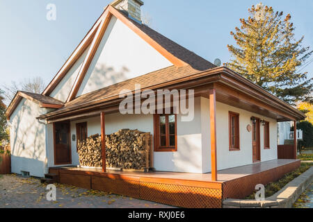 Old 1877 French regime style house facade with white stucco finish, reddish brown stained lattice-work and period reproduction wooden windows and cord - Stock Photo
