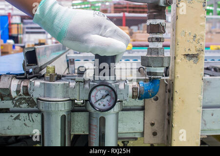 The hand of technician adjust the pressure setting of the wind on regulator. In the pneumatic system - Stock Photo
