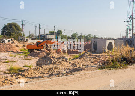 Excavators are digging soil To set up a large drainage pipe close to the road in the city area - Stock Photo