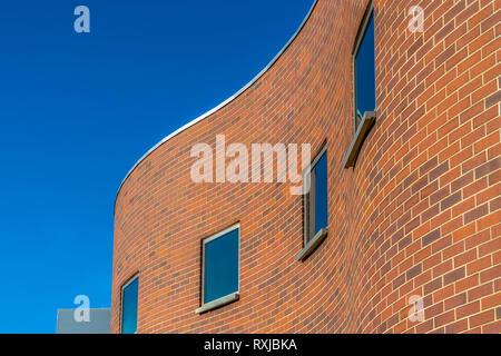 Curvy brick building exterior against blue sky - Stock Photo