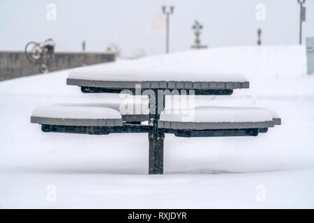Round table with seats covered with snow in winter - Stock Photo