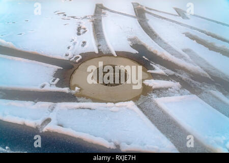 Sewer manhole cover on snow covered road - Stock Photo