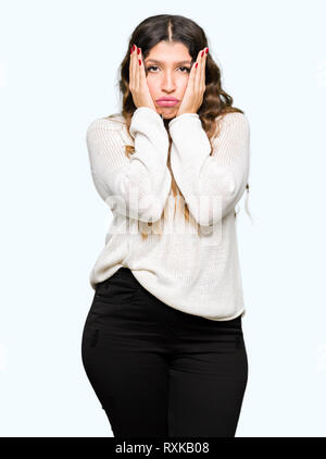 Young beautiful woman wearing white sweater Tired hands covering face, depression and sadness, upset and irritated for problem - Stock Photo