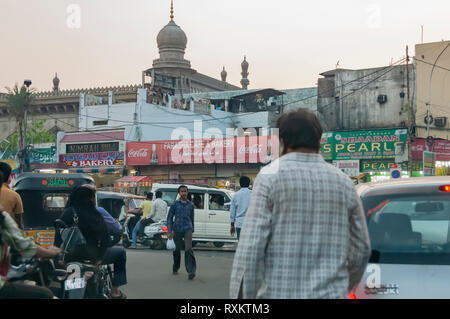 Jaywalking in the busy and crowded streets around Charminar, Hyderabad, Telangana, India. The streets are crammed with all sorts of vehicular traffic. - Stock Photo