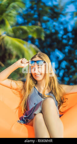 Summer lifestyle portrait of pretty girl sitting on the orange inflatable sofa on the beach of tropical island. Relaxing and enjoying life on air bed - Stock Photo