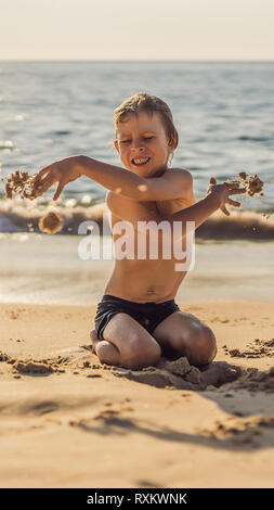 The boy screams and freaks out on the beach, throws sand. Tantrum concept VERTICAL FORMAT for Instagram mobile story or stories size. Mobile wallpaper - Stock Photo