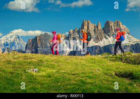 Sporty healthy active woman group of hikers with colorful backpacks and mountain equipment walking on the mountain ridge, Dolomites, Italy, Europe - Stock Photo