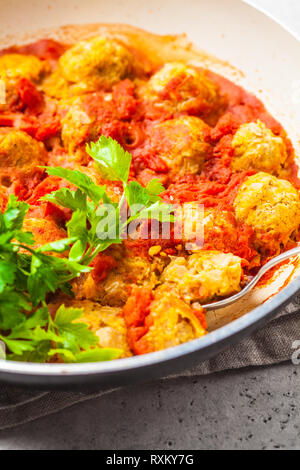 Baked vegan bean meatballs in tomato sauce with parsley. Plant based food concept. - Stock Photo