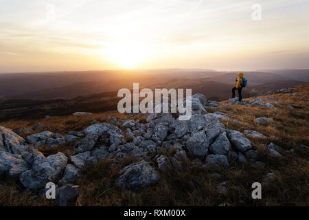 Boy hiking on a grass covered mountain at sunset, Golic, Slovenia - Stock Photo