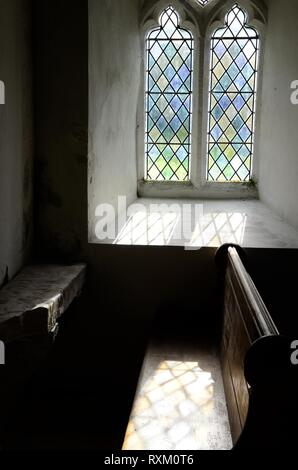 Light shining through a stained glass window on an old church pew and Ogham stone early Christian sculptured stone St Odoceus Church Llandawke Wales - Stock Photo
