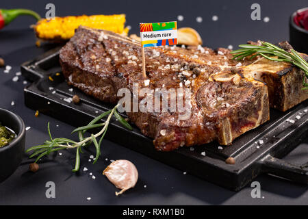 Delicious beef steak on black stone cutting board. Grilled meat served with grilled corn, garlic, rosemary, sauces, chilli and salt on black backgroun - Stock Photo