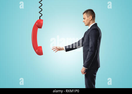 Side view of businessman standing and reaching out for big red landline phone receiver dangling down on wire from above. - Stock Photo