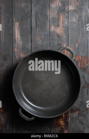 Empty pan on dark wooden kitchen table top view - Stock Photo