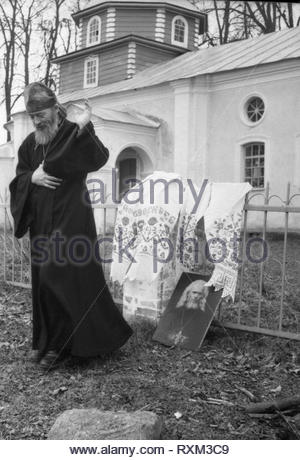The priest Nikolay served in rural church in Smolensk region. I captured him when he finished pray for soul of his died father,who was priest as well. The portrait of his father he put by fence near parish. - Stock Photo