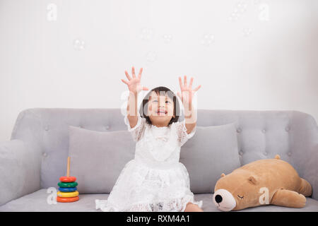 Pretty happy little girl in casual wearing sitting on sofa with toy dog and smiling - Stock Photo