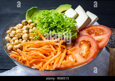 Close-up view of buddha bowl on a rustic table. Vegan meal of chickpeas, salad, vegetables, tofu and avocado - Stock Photo