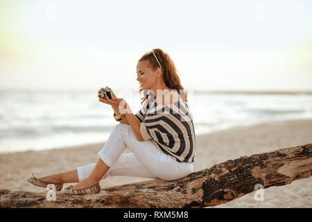 smiling trendy solo traveller woman in white pants and striped blouse on the beach at sunset viewing photos on camera while sitting on a wooden snag. - Stock Photo
