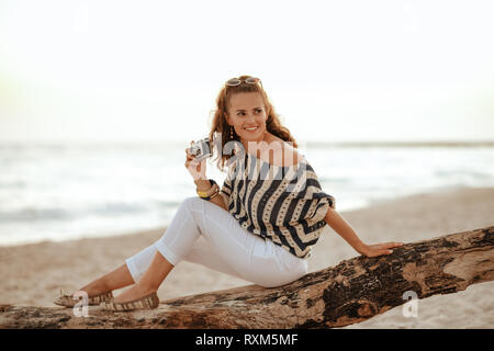 smiling elegant solo traveller woman in white pants and striped blouse with retro film photo camera looking aside while sitting on a wooden snag on th - Stock Photo