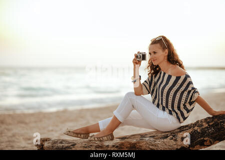 smiling elegant traveller woman in white pants and striped blouse taking photos with retro photo camera while sitting on a wooden snag on the seacoast - Stock Photo