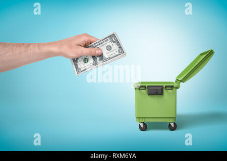 Male hand throwing bundle of money dollars into green trash bin on blue background - Stock Photo