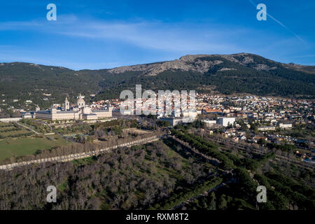 Aerial view of the Monastery of El Escorial at sunrise in spring with the Guadarrama mountains at the bottom - Stock Photo