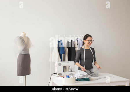 Dressmaker, technologies, fashion designer and tailor concept - young female fashion designer working in her showroom - Stock Photo