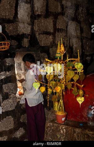 Cambodia, Phnom Penh, Oudong, priest at window of small vihara by symbolic golden bo tree - Stock Photo