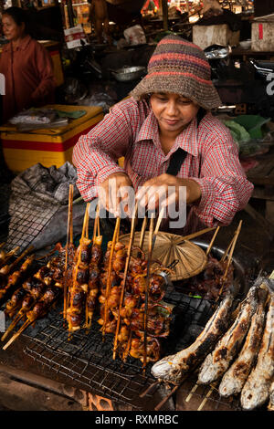 Cambodia, Phnom Penh, Oudong, food market, bush meat stall, woman selling small birds cooked over charcoal grill - Stock Photo