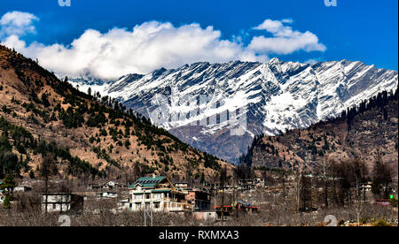 Snow Covered Himalayan Mountain Ranges with Clear Blue sky and White Cumulus Clouds in Manali, Himachal Pradesh, India. A Perfect Summer Destination. - Stock Photo
