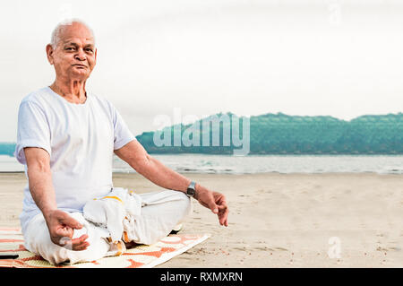 Healthy Old man, a Super Senior Citizen, performing Yoga and Meditating on a beach side by sitting in Lotus Posture - Stock Photo
