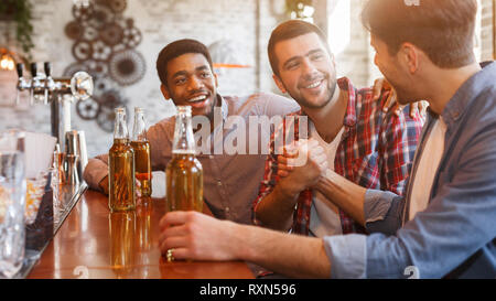 Happy to finally meet old friends in bar - Stock Photo