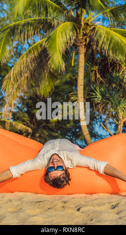 Summer lifestyle portrait of man sitting on the orange inflatable sofa on the beach of tropical island. Relaxing and enjoying life on air bed VERTICAL - Stock Photo
