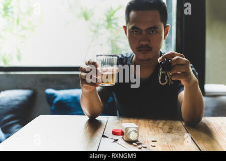 Man holds glass of whiskey and car keys with pills on the table.