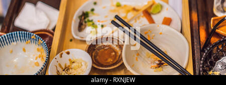 Messy table after meal in Japanese restaurant. Dirty, finish meal, leftovers concepts BANNER, LONG FORMAT - Stock Photo