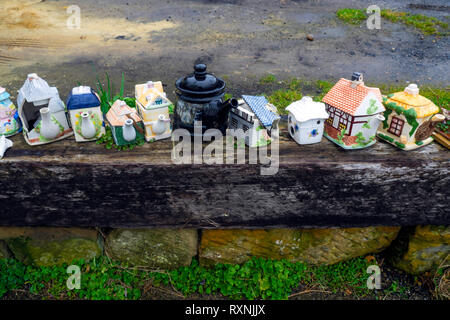 A row of old fashioned fancy teapots some damaged used as ornaments in a garden by the sea on the Yorkshire Coast - Stock Photo