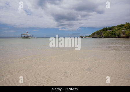 outrigger dive boat at the sea shore on the white sand, in a tranquil summer sunny day background photo - Stock Photo