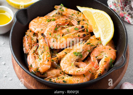 Fried shrimps in shell with parsley, coriander, garlic and oil in pan. Tasty mediterranean cuisine, vegetarian food, healthy protein - Stock Photo