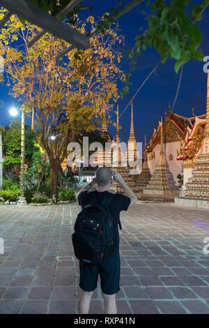 Man takes photos of buddist temple Phra Maha Chedi at night, Bangkok, Thailand - Stock Photo