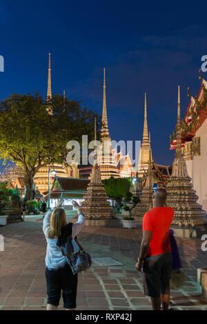 Tourists take photos of buddist temple Phra Maha Chedi at night, Bangkok, Thailand - Stock Photo