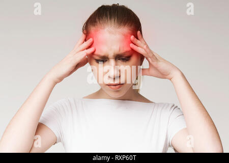 Woman suffering from headache, touching her temples - Stock Photo