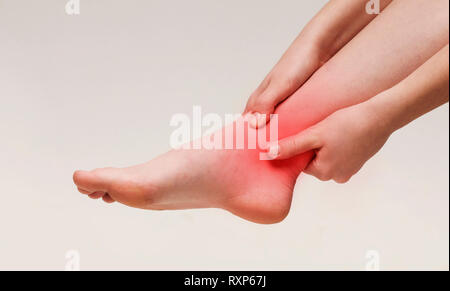 Woman suffering from pain in ankle closeup - Stock Photo